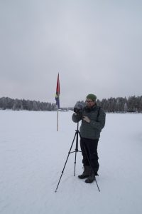 A male stands behind a camera on a tripod in a field of snow, with trees in the background.