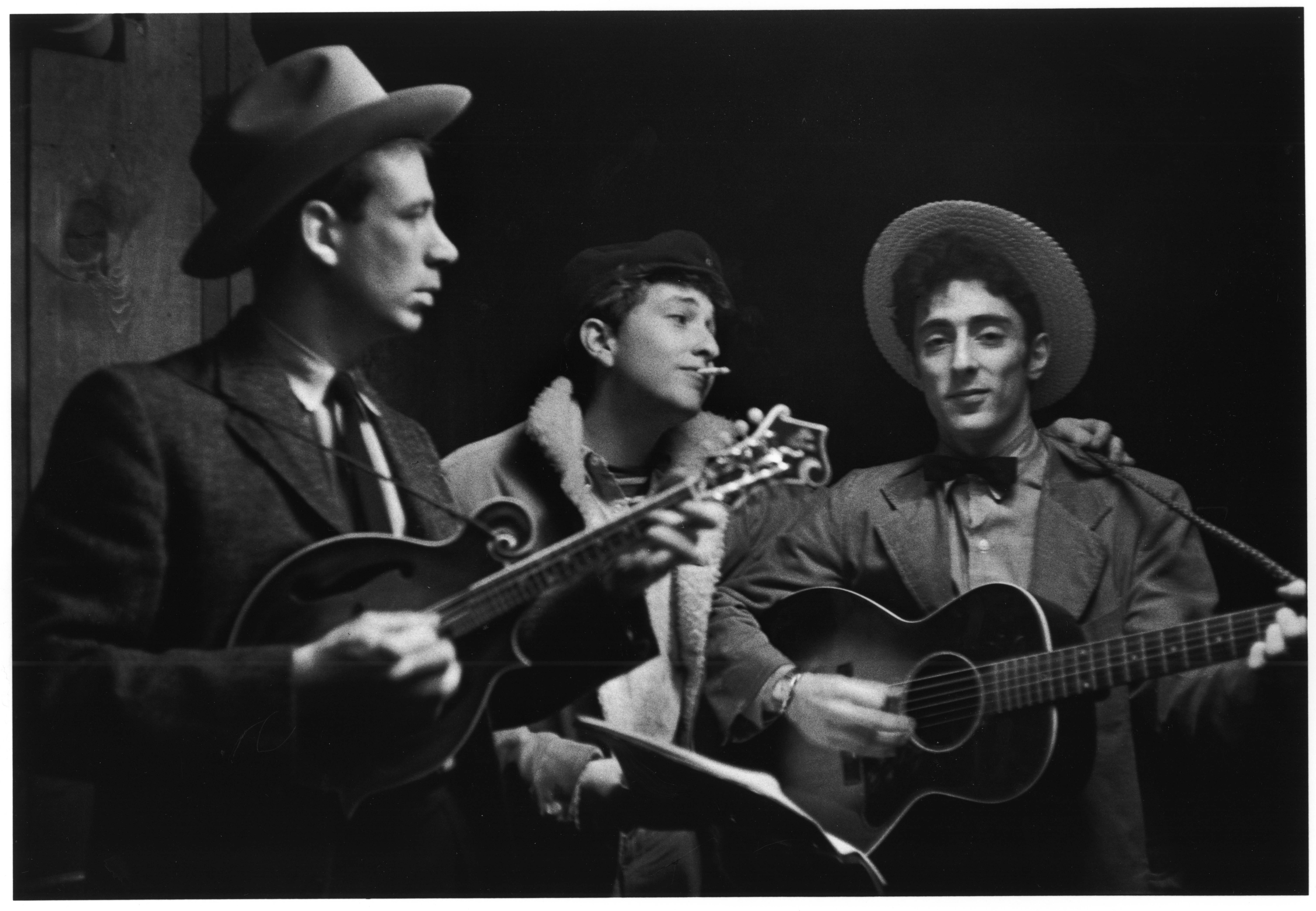 Three men in hats playing acoustic instruments.