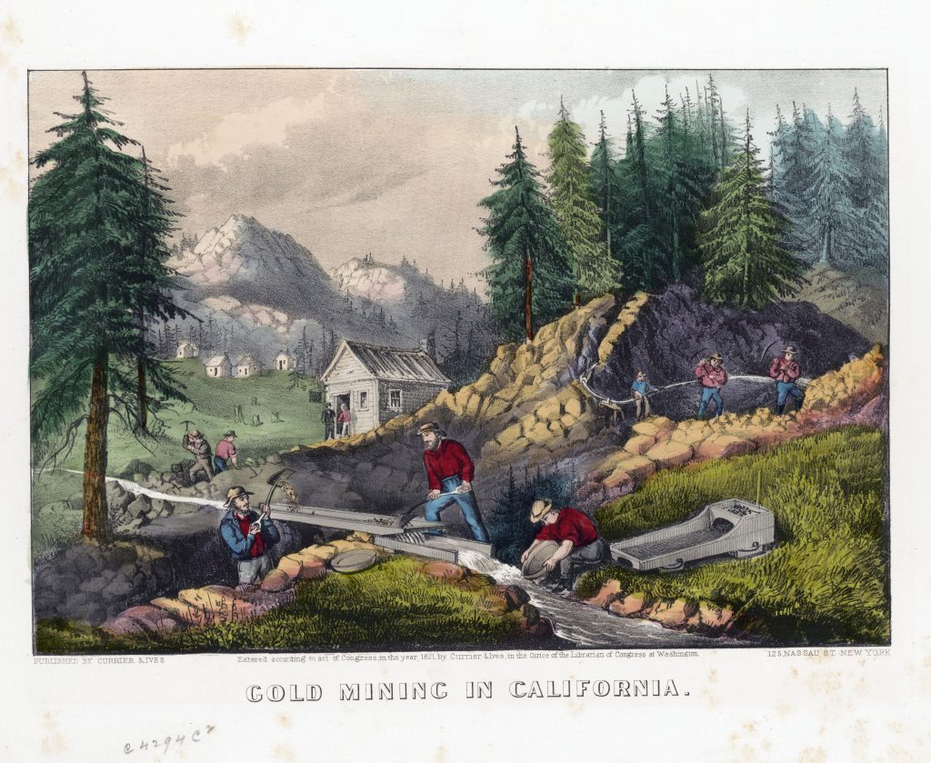 Gold miners shoveling sand from stream into sluice while one miner pans for gold in the same stream, small building and mountains in the background.