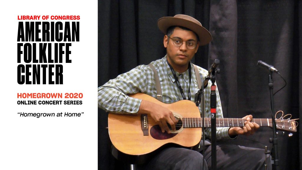 Dom Flemons seated with guitar