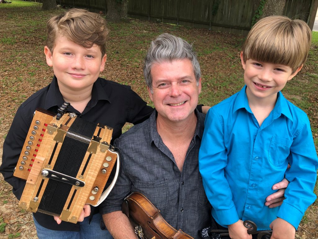 Burke Riley, 10 years old, holding a diatonic button accordion, Steve Riley, the boys' father, holding a fiddle. Dolsy Riley, 7 years old, holds a triangle.