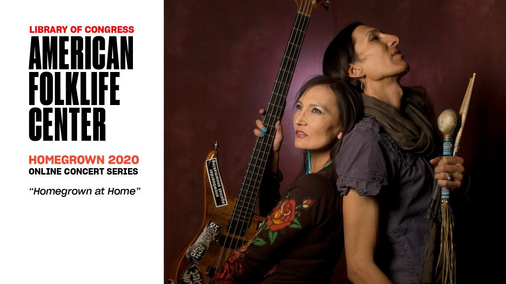Jeneda and Clayson Benaly stand back to back. She holds an electric bass, he holds drumsticks and a rattle.