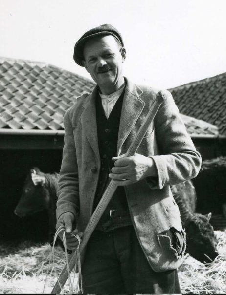 Three-quarter-length portrait of Luke Stanley carrying a farming tool.