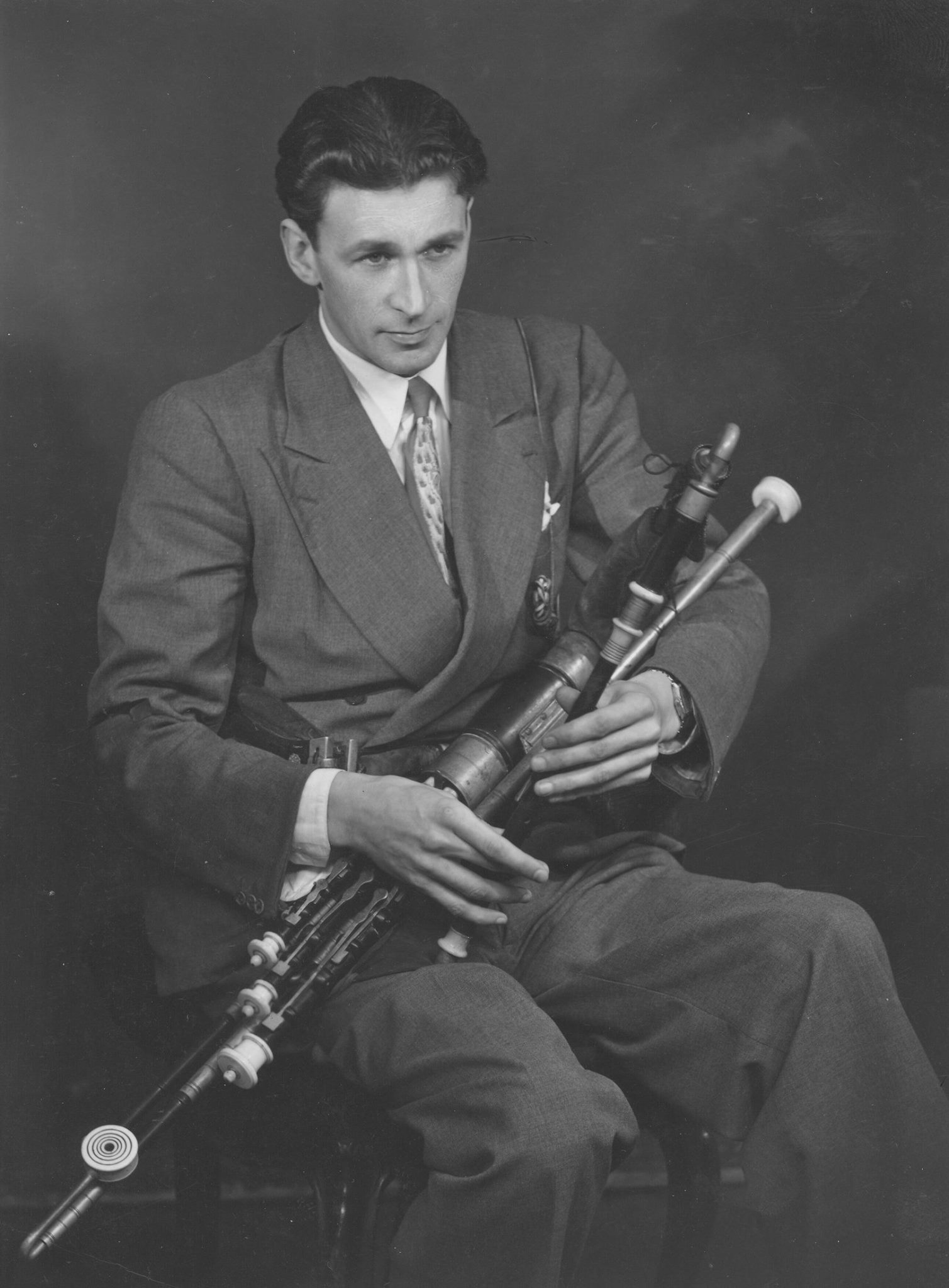 Séamus Ennis, seated in a chair playing the Irish Uilleann bagpipes.