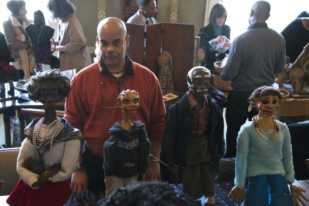 An African American man stands behind a display of four hand-crafted African American puppets.