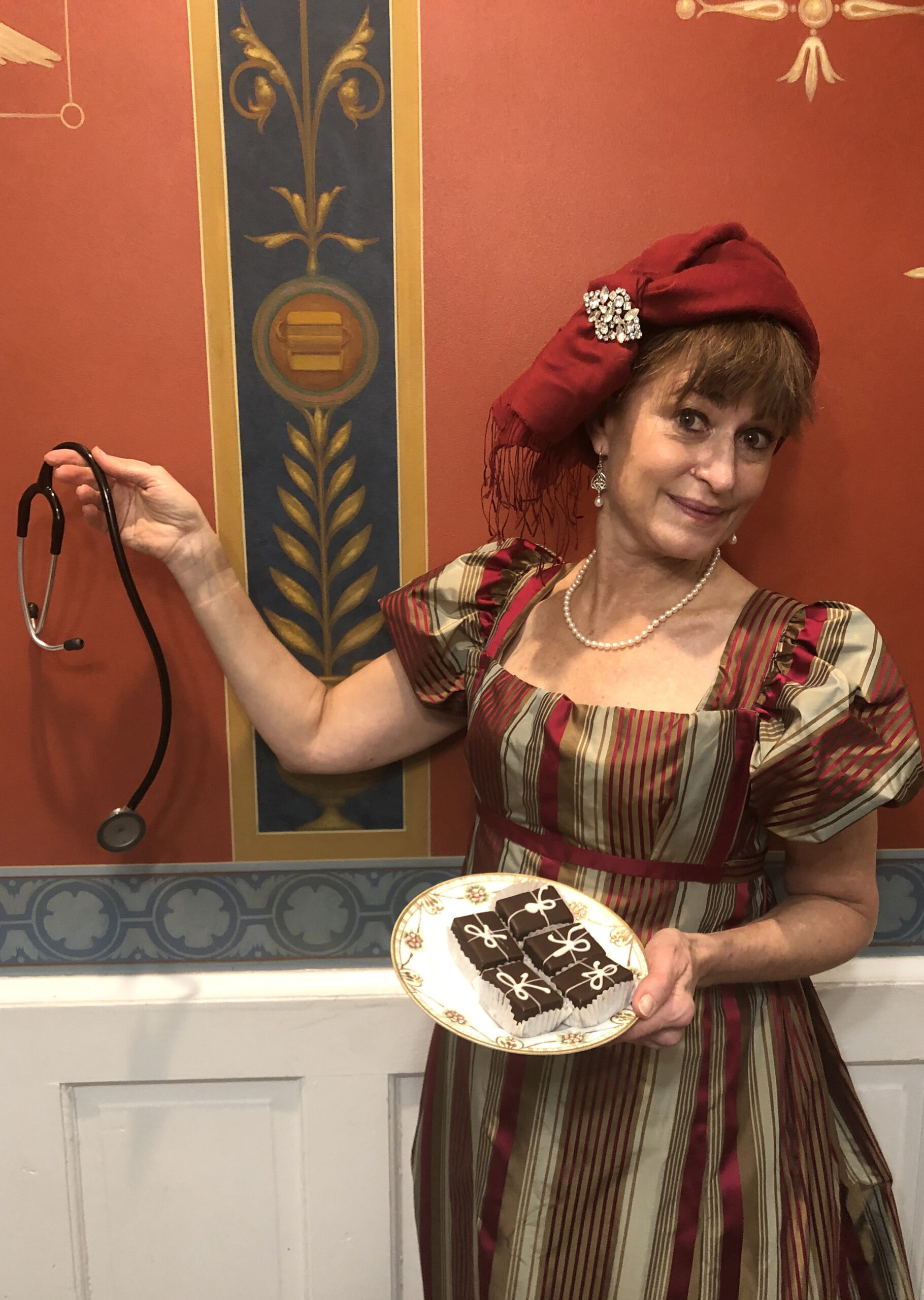 Doctor Dolley Madison, portrayed by Thea Austen, holds a plate of chocolate cakes in one hand and a stethoscope in the other.