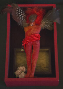 A handmade African American doll in red displayed in a box. Instead of arms, the doll has wings made of feathers.