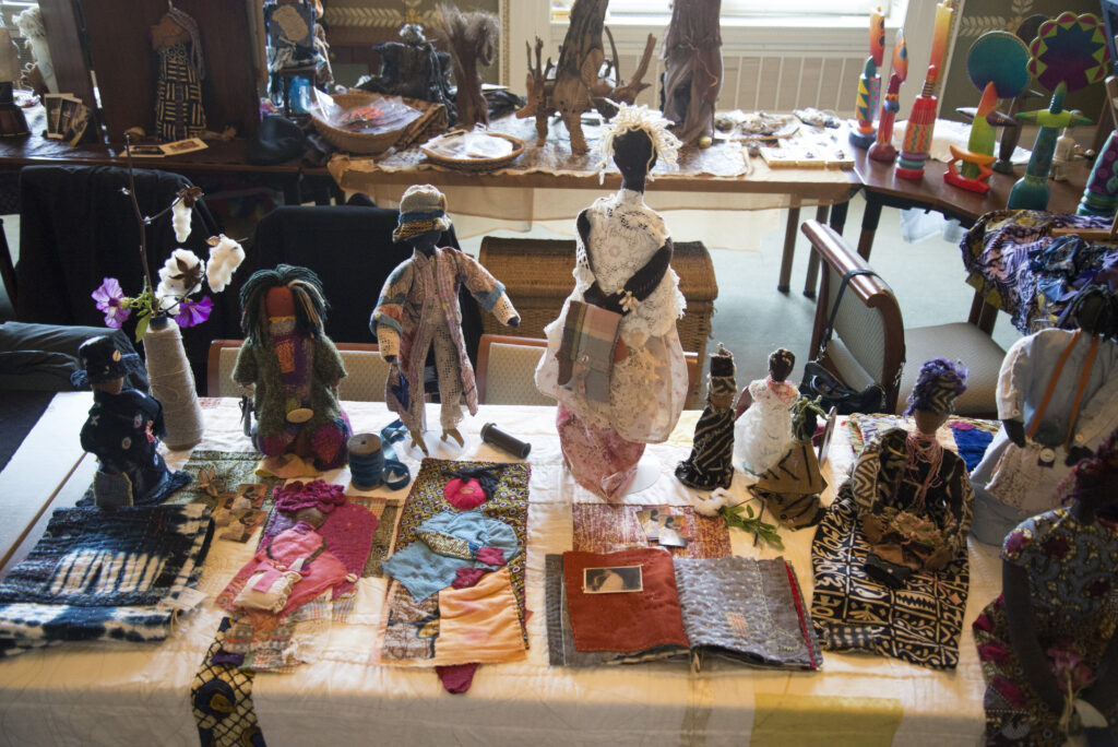 A diplay of African American dolls made of fabric and other media along with fabric books and fabric art.