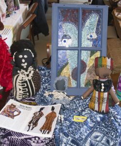 Three African-style fabric dolls decorated with cowrie shells with a mixed-media wall hanging and batik fabrics.