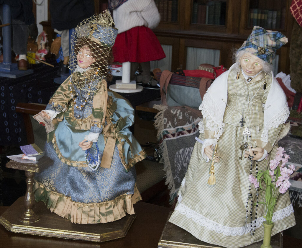 Two handmade female dolls in nineteenth century dresses. Both represent light-skinned African Americans.