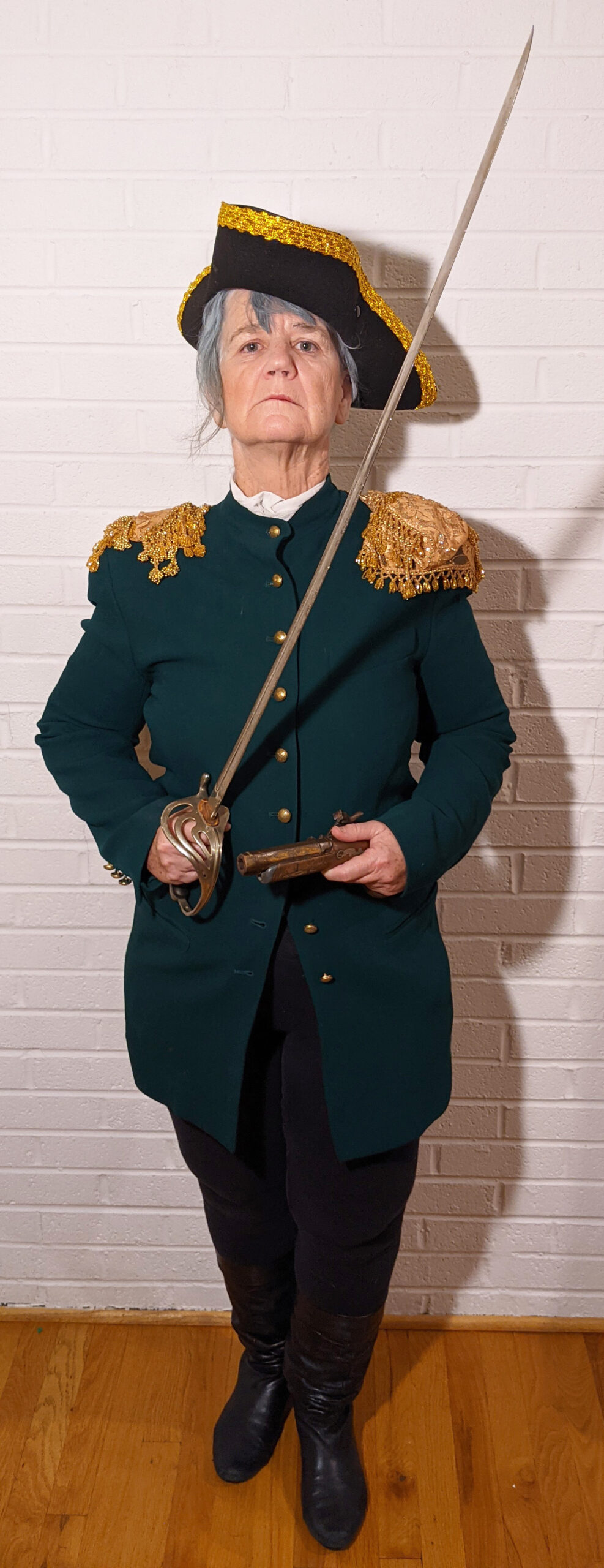 Full length portrait of Hope O'Keeffe as George Washington, with a sword in one hand and a flintlock pistol in the other.