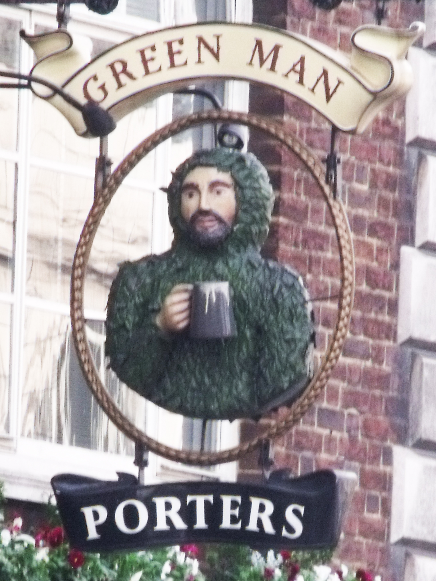 Green Man pub sign in Euston Road, London. The sign show the head and shoulders of a man; he is covered in green leaves except for his face. He holds a mug of beer in his right hand.