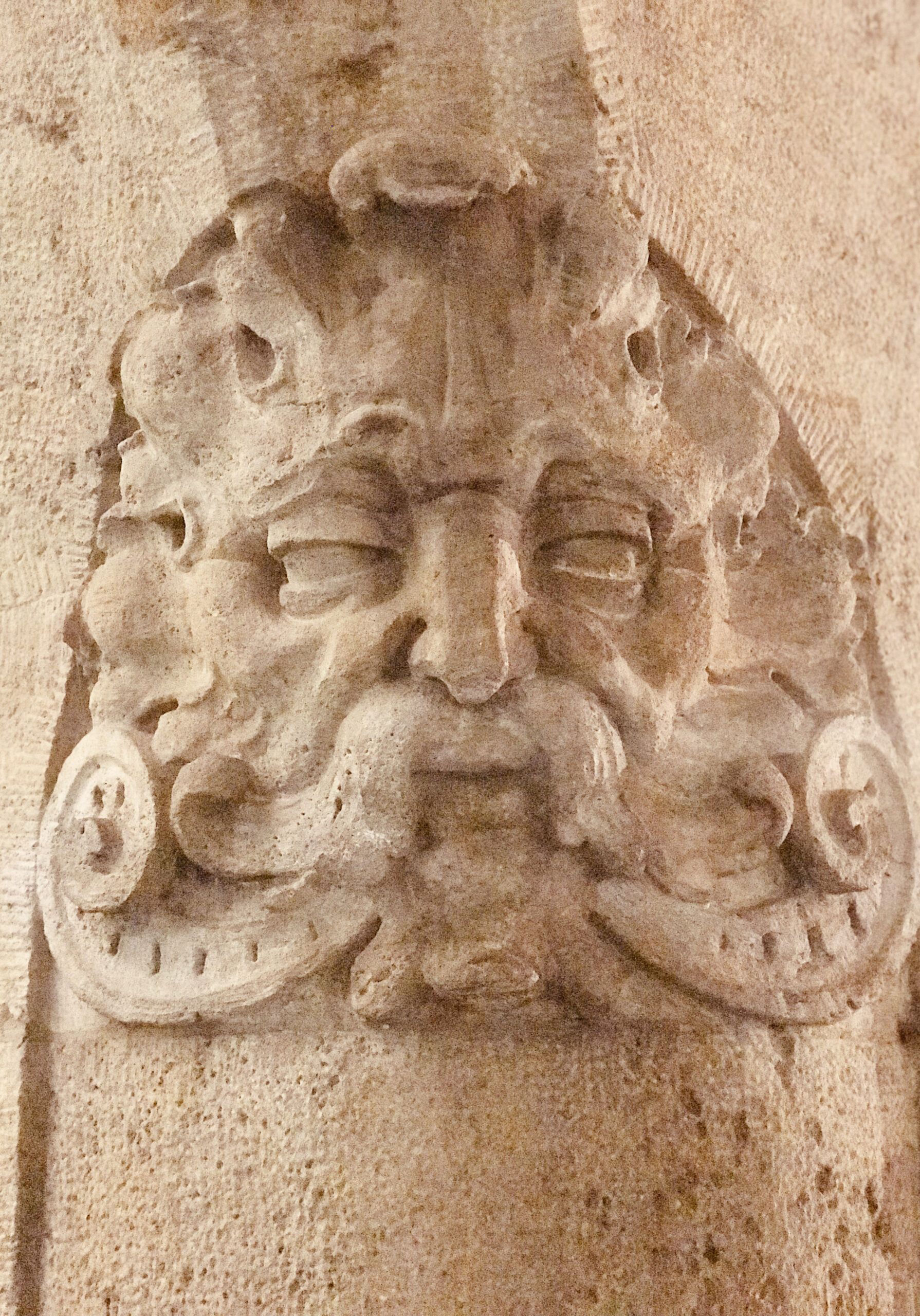 A foliate head carved into a stone column capital on a 1589 building in Munich, Germany.