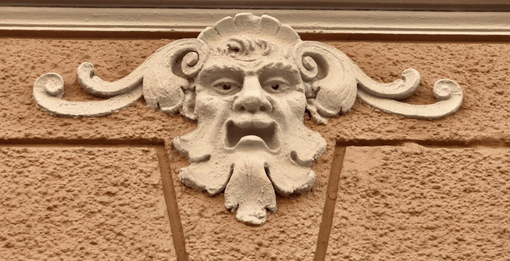 A sculpted face on the façade of a building. Its hair and beard are made of leaves.