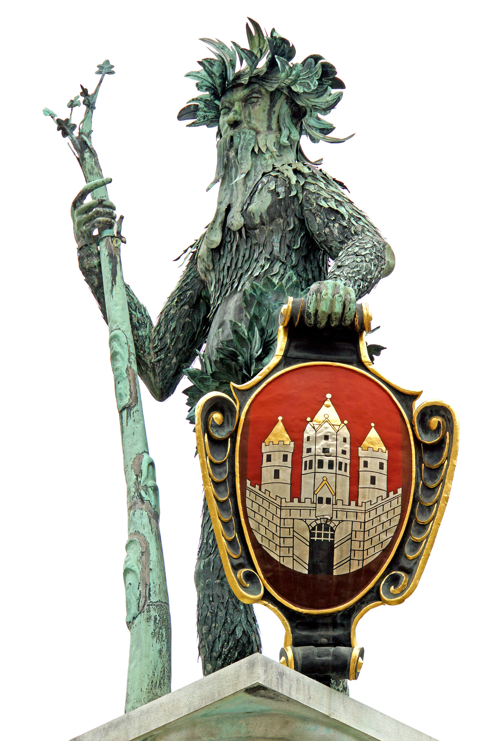A photo of a green copper statue of a bearded man covered in leaves with a leafy garland on his head, holding in one hand a bough about as tall as he is, and in the other hand a shield with a coat of arms.