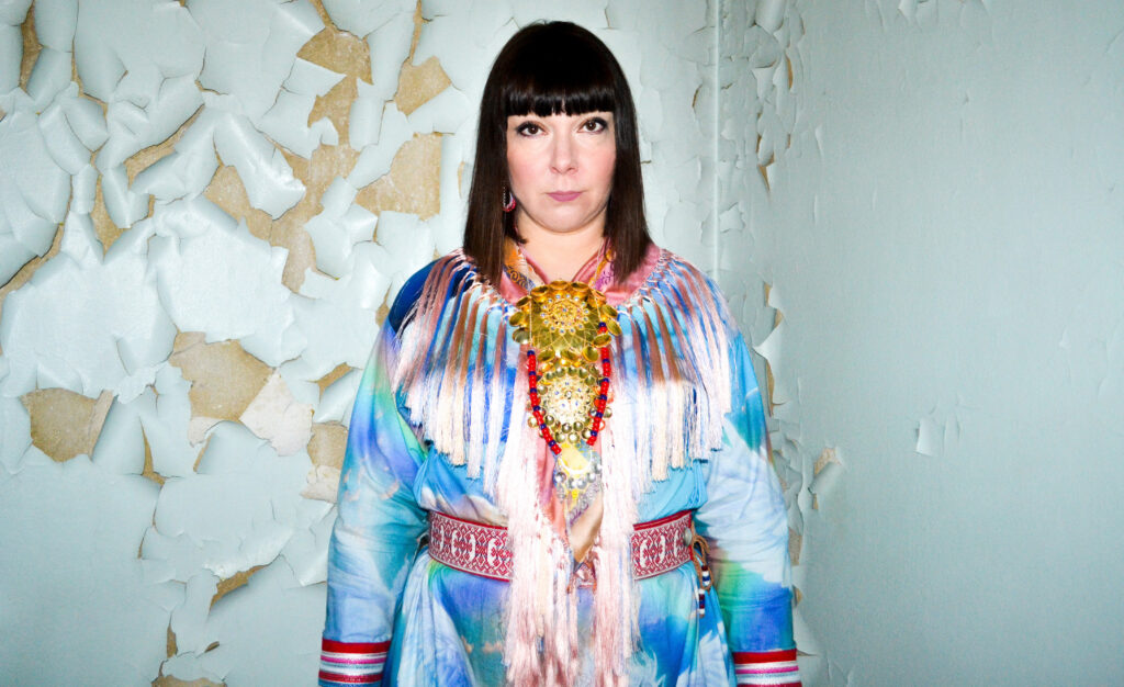 Ánnámáret, a woman in traditional Sami attire, stands next to a wall with peeling paint