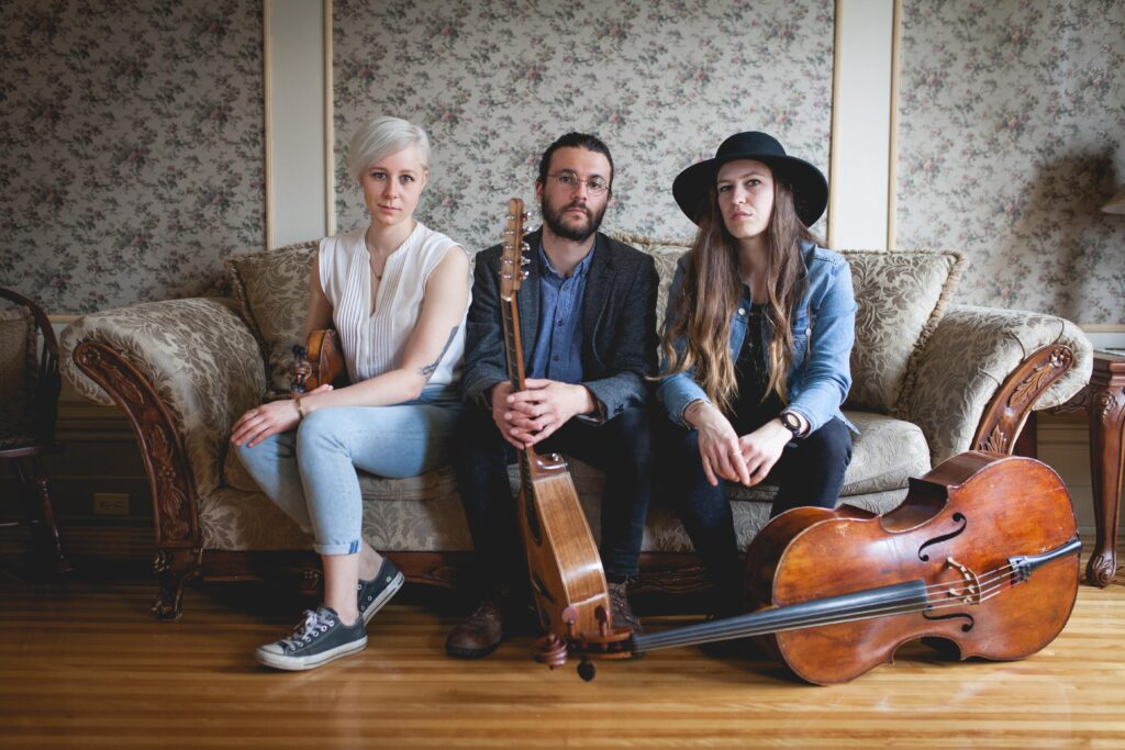 The members of É.T.É sit on a sofa. Élisabeth Moquin holds a fiddle, Thierry Clouette holds a bouzouki, and Élisabeth Giroux's cello lies by her feet.