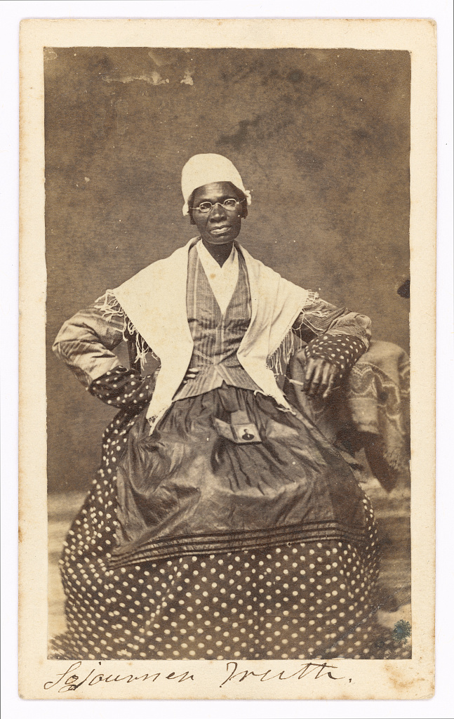 Photograph shows portrait of abolitionist Sojourner Truth wearing polka dotted dress and holding cased photograph of her grandson.