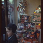 Boy beside store window display of Christmas ornaments
