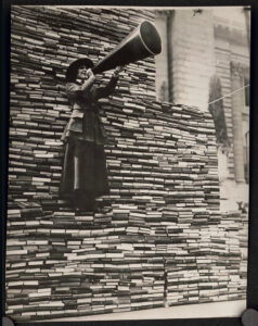 Photograph shows a woman standing on a pile of books speaking into a megaphone for an American Library Association War Service promotion to collect books for soldiers fighting in Europe
