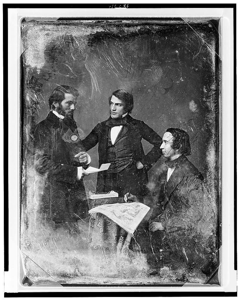Three men dressed in suits talking. Two are standing, one is sitting.