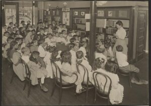 Photograph showing a librarian telling an Ojibwa legend to a roomful of children at the Queens Borough Public Library.