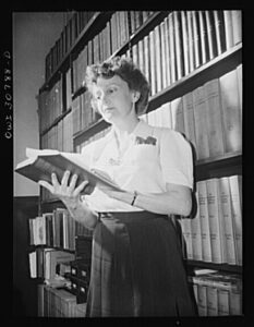 Woman standing in front of shelves of books, reading a book.