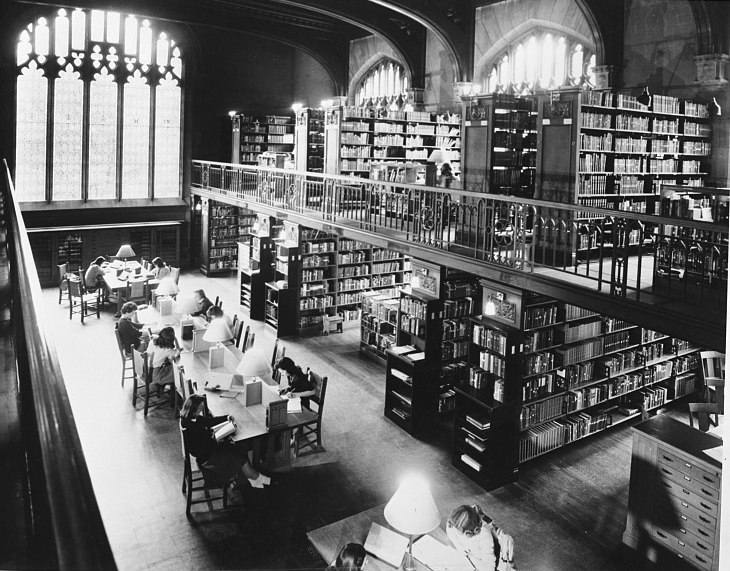 Image of a library, taken from above, looking down at students studying at tables. The outside of room has shelves of books.