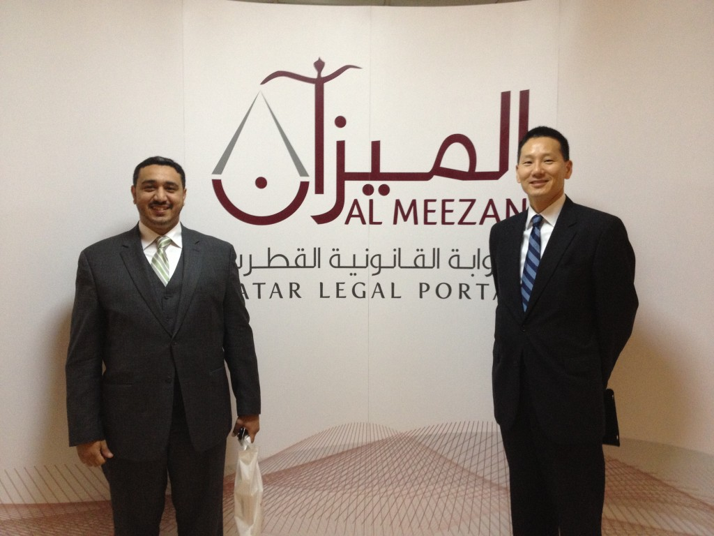 George Sadek and David Mao stand in front of the banner for the new Qatar legal portal, Al Meezan.