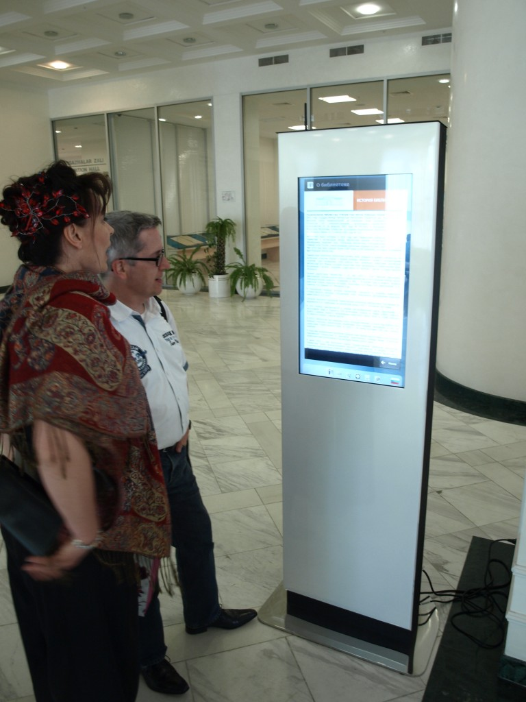Visitors read an information kiosk in the lobby of the National Library of Uzbekistan.