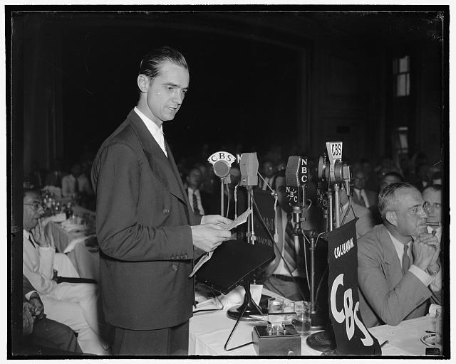 Howard Hughes speaking before the Press Club. Washington, D.C., July 21. Howard Hughes, speaking at the National Press Club today, before hundreds of government officials and representatives of foreign governments. Hughes today envisioned a future in aviation when giant flying boats, almost as large as modern ocean liners, will fly the Atlantic under conditions in which the element of luck will play no part, speaking at the luncheon in his honor, he described in detail the type of flying craft and equipment he believes the future will see but which is now nothing more than an aeronautical engineers dream. Photograph by Harris & Ewing (July 21, 1938). Library of Congress Prints and Photographs Division. //hdl.loc.gov/loc.pnp/hec.24844