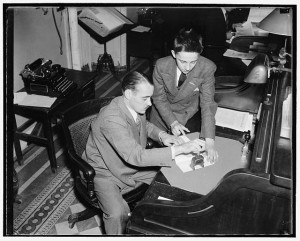 How a bill becomes a law. Delivered to the chief bill clerk by a page boy, the bill is given a number and sent to the Government Printing Office for printing. William McDermott, chief bill clerk of the house, is shown numbering a bill brought to him by page John Jurgensen. Photograph by Harris and Ewing. (Created 1937 or 1938). Courtesy of the Library of Congress Prints and Photographs Division. //loc.gov/pictures/resource/hec.24079/