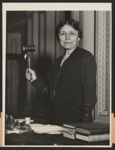 Photographs shows Mrs. Hattie Wyatt Caraway, Senator from Arkansas, half-length portrait, standing at rostrum of the Senate, holding gavel in raised right hand, facing front.