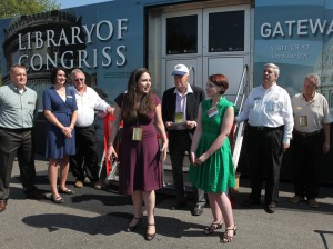 "Abby and Emily Rapoport on Sept. 25 prepare the cut a ceremonial ribbon on the ""Gateway to Knowledge"" traveling exhibition, which the two funded. Librarian of Congress James H. Billington is pictured between them. At left are docents Josh and Abigail Van Gelder."