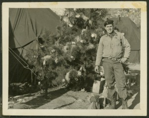 "Nicholas W. Phillips in front of Christmas tree decorated with beer cans. ""Korea Xmas '52"" on reverse. Nicholas W. Phillips Collection, Veterans History Project."
