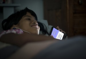 Young patron reads at bedtime using her smartphone.