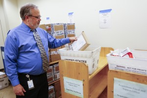 Richard Yarnell reviews materials in the acquisitions mailroom where they are sorted by country of origin.