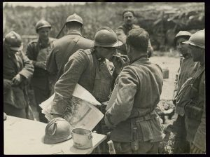 Italian soldiers lighting cigarettes, one holding illustrated newspaper, Piave River, Italy, October 1918. Prints and Photographs Division.