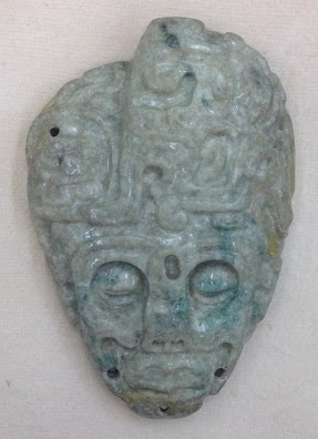 Copan Style Jade Pendant from the Jay I. Kislak Collection representing the head of a prisoner who has had the right side of his skull removed, exposing the brain. Late Classic Maya, 600-900 CE. Geography and Map Division, Library of Congress.