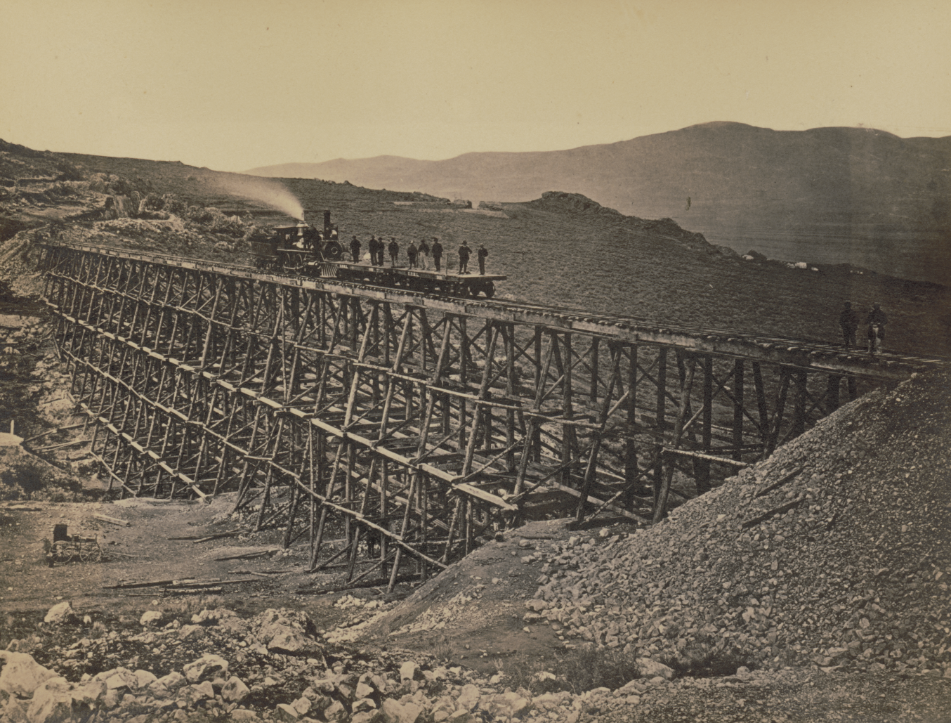 Railroad trestle spanning valley, with train and platform full of workers on track.