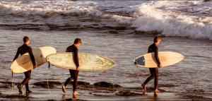 Photo of Three surfers take to the waves at Butterfly Beach in Montecito