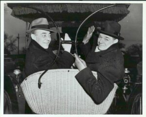 Rodgers and Hammerstein seated in a surrey with fringe on top.