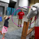 A young festivalgoer tries her hand at a ring toss at the Wells Fargo booth during the National Book Festival, September 5, 2015. Photo by Shawn Miller.
