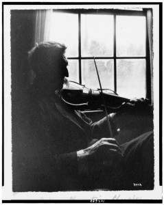 I Love Mountain Music; photo of man sitting in a chair by the window playing fiddle