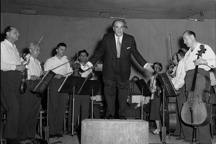 "Composer Heitor Villa-Lobos bows to the public after his concert at the ""Ohel Shem"" Hall in Tel Aviv, June 1952. Public domain."