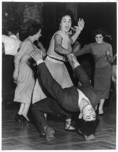 Rock 'n' Roll dancing in a respectable London Dance Hall. Young woman holding young man by hand, as he leans backwards with his head close to the floor.