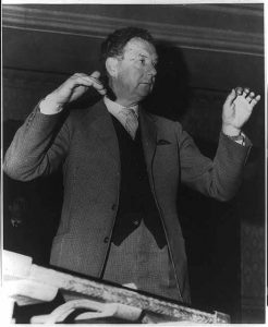 Black and white photograph of Benjamin Britten, half-length portrait, conducting, facing right.