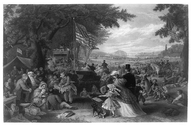 Print shows a large gathering of people picnicking, playing games, and enjoying the Independence Day celebration outdoors among large trees and open lawn, with a distant view of a railroad train passing and of ships on a waterway in the background.