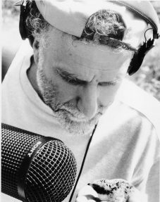 Jim Metzner holds a microphone to record the sounds of a baby bird