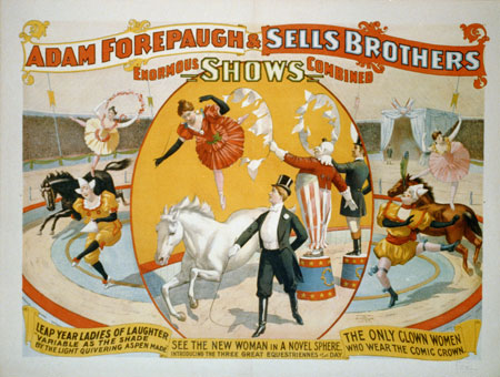 Women circus performers and clowns with woman ringleader wearing tuxedo and top hat.